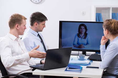 Three workers having business conference online with colleague