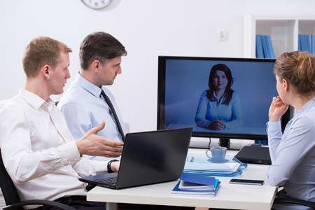 Tres trabajadores que tengan conferencia de negocios en línea con su colega Foto de archivo - 42424449