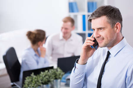 transact: Middle aged handsome businessman talking on the phone with client