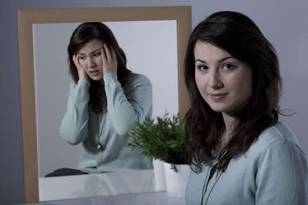 the borderline: Scared young woman suffering from manic depression Stock Photo
