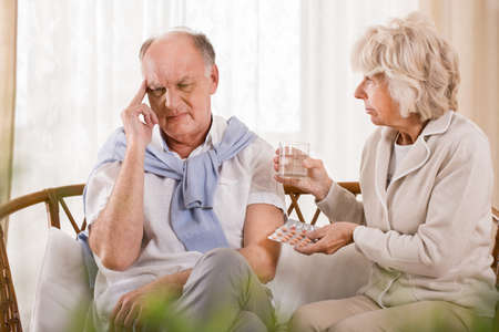 taking a wife: Aged man taking pills from wife for terrible headache Stock Photo