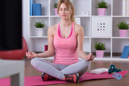 floor mat: Sitting in lotus position on exercise floor mat