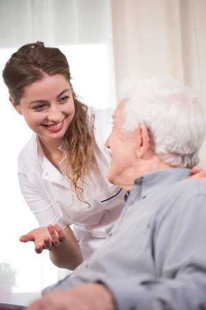 Young nurse taking care of an elder pensioner Stockfoto