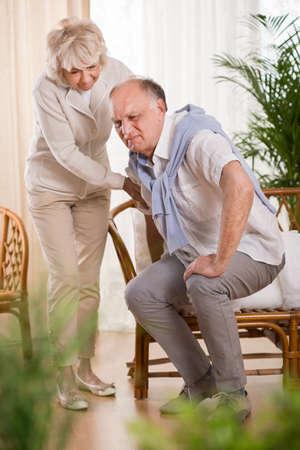 Senior man met pijn in de rug en zijn behulpzaam liefhebbende vrouw