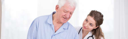 benevolent: Weakened elder man supported by young nurse