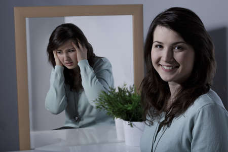 on mirrors: Smiling pretty young girl with bipolar disorder