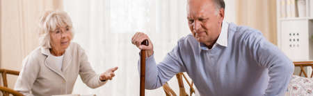 Aged man with backache trying to stand up