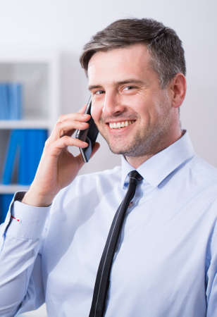 transact: Portrait of handsome smiling businessman with mobile phone