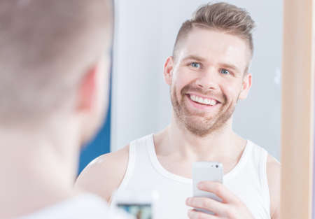 narcissistic: Smiling handsome young man doing selfie in mirror