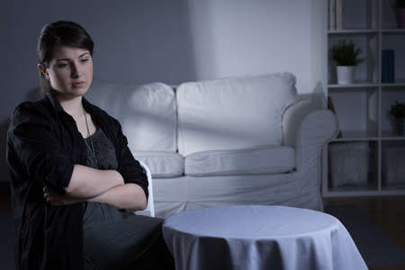 Troubled young woman with depression sitting alone at home