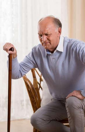 personas de espalda: Hombre mayor con bast�n tratando de ponerse de pie