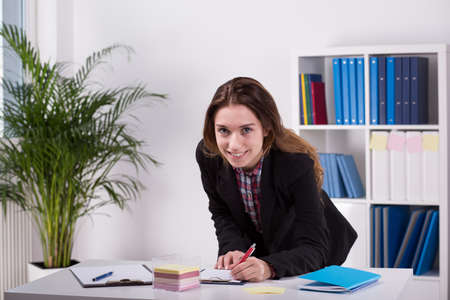 working desk: Image of young woman working in agency Stock Photo