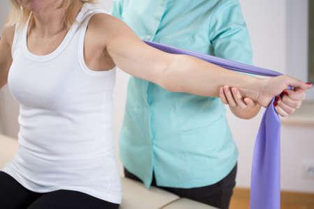 Mujer en la oficina fisioterapeuta ejercer con la banda Foto de archivo - 42424953
