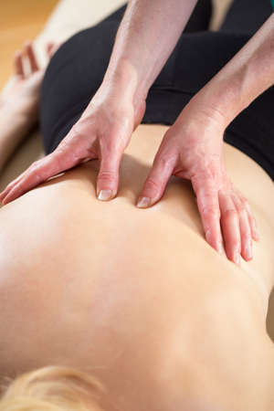 Close-up of masseur pressing the painful points on patients back