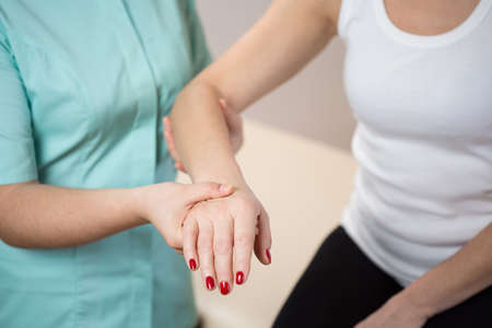 color therapy: Close-up of pysiotherapist holding womans forearm