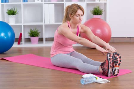 girl with towel: Stretching after training on the exercise floor mat Stock Photo