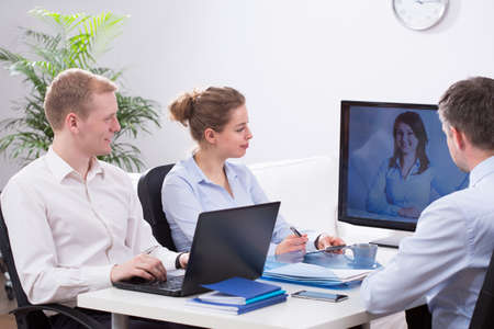 video conference: Young busy creative businesspeople and video conference Stock Photo