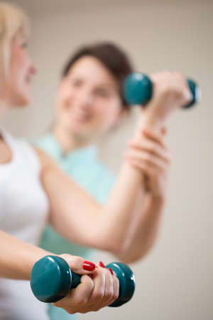Close-up of blue dumbbell at exercising woman's hand 스톡 콘텐츠