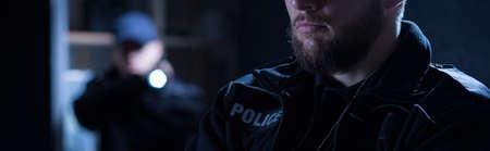 警察官のパートナーは、懐中電灯を保持しています。