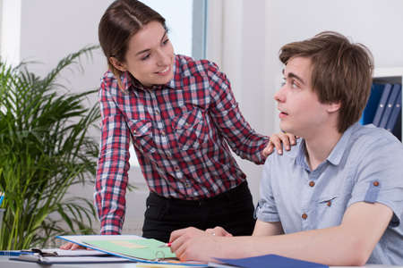 flirt: Young woman flirting with co-worker in the office Stock Photo