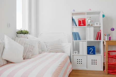 studie: Současná výzdoba dětského pokoje s pohovkou a knižní police Reklamní fotografie