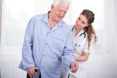 osteoporosis: Los jóvenes cuidan el cuidado de un hombre mayor Foto de archivo