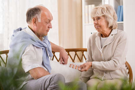Loving wife giving the pills to her older husband