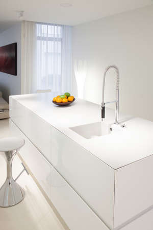 Bowl of fruits on white worktop in modern kitchen