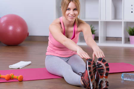 muscle girl: Woman sitting on the floor and bending down