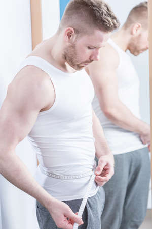 narcissism: Muscular fit man checking his waist circumference Stock Photo
