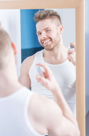 narcissistic: Handsome smiling man using new nice perfume