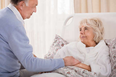 Ouderen ondersteunende man en zijn oudere zieke vrouw Stockfoto