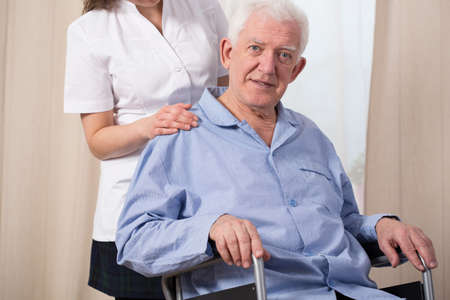 senility: Pensioner dressed in pyjama and sitting in a wheelchair