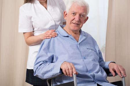 enfermo: Pensionista vestido con pijama y sentado en una silla de ruedas