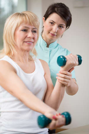 physiotherapists: Elderly woman exercising with dumbbells at physiotherapists office