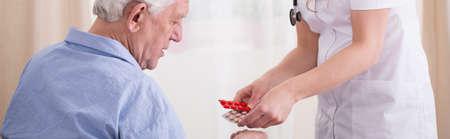 medications: Nurse giving some medications to elder man
