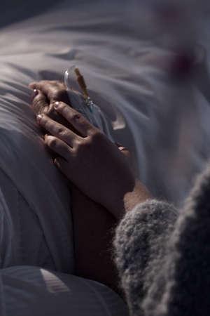 enfermo: Primer plano de una mujer joven sosteniendo la mano de su abuela
