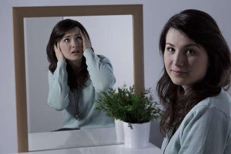 falso: Mujer muy sonriente joven que oculta sus emociones negativas