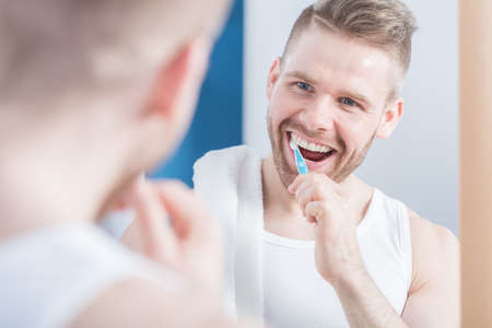 narcissistic: Pretty young man brushing his perfect teeth