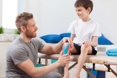 junge nackte frau: Kleine Patienten mit Kinesio-Taping nach Knieverletzung