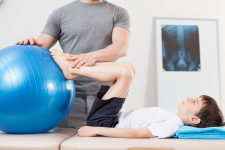 physiotherapist: Small patient doing exercise with fitness ball