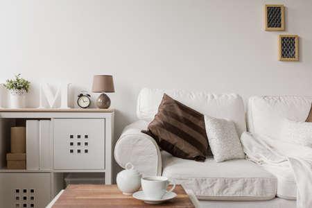 divan: Sof� blanco y c�moda en el sal�n