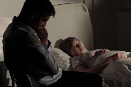 malignant neoplasm: Sad father sitting by his dying daughter with cancer