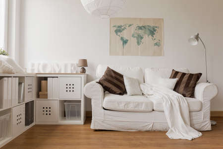 minimalist apartment: White sofa and commode in cozy living room