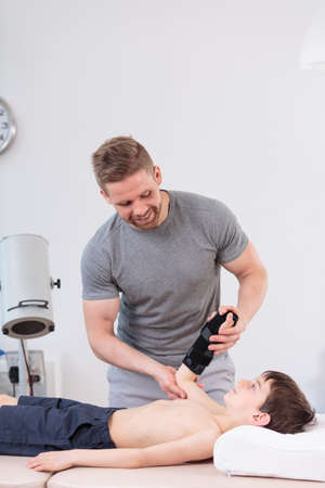 lamp: Young male physiotherapist working with small patient