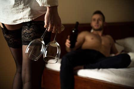 enamorados en la cama: La mujer llevaba medias de celebración de Copa de vino Foto de archivo