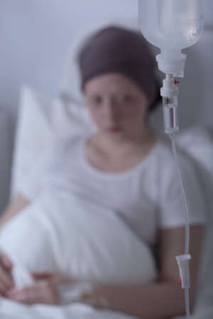 bald girl: Close-up of patients drip who is young girl with cancer