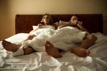 joven fumando: Pareja joven tumbado en la cama