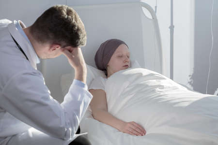 oncologist: Young girl with cancer in hospital and worried oncologist