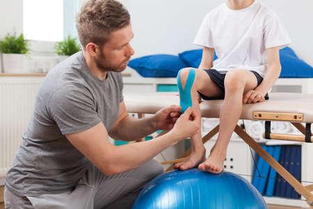 fisioterapia: Fisioterapeuta aplicar cinta médica paciente joven Foto de archivo